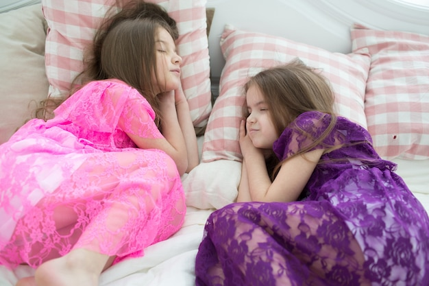 Mooie meisjes in roze en paarse jurken slapen in bed