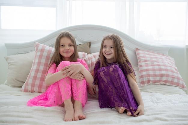 Mooie meisjes in roze en paarse jurken zitten op bed
