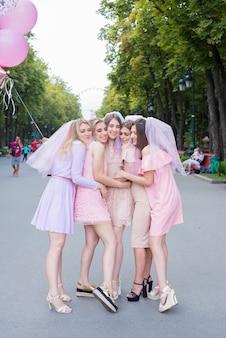 Mooie meisjes in roze jurken vieren vrijgezellenfeest in het park