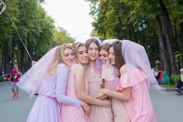 Mooie meisjes in roze jurken vrijgezellenfeest vieren in het park en knuffelen