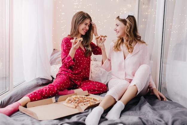 Mooie meisjes in sokken en pyjama's praten rond en maken een grapje. indoor portret van positieve dames pizza eten in bed.