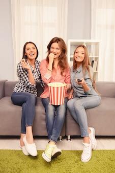 Mooie meisjes kijken naar grappige komedie en eten popcorn