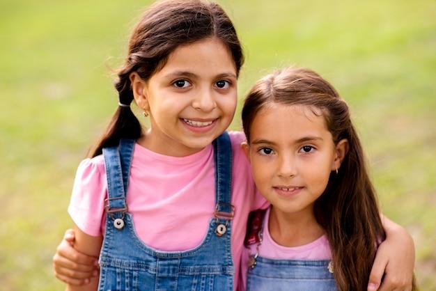 Mooie meisjes knuffelen elkaar terwijl glimlachen