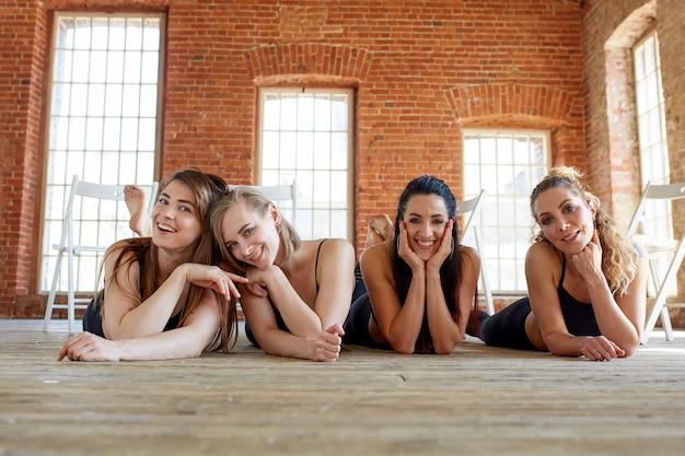 Mooie meisjes liggen op de vloer en kijken naar de camera.