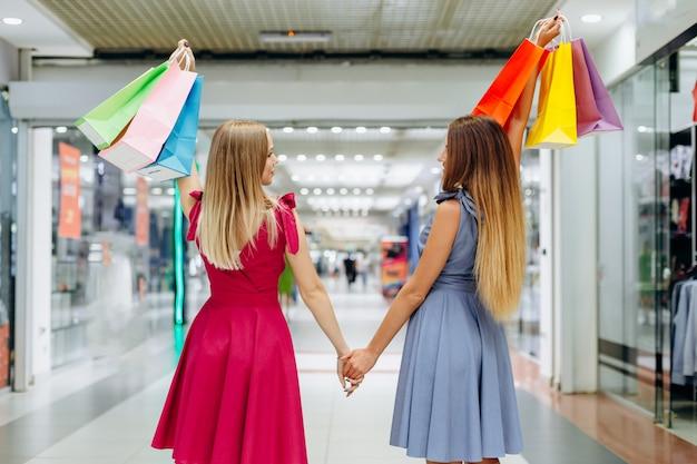 Mooie meisjes lopen rond het winkelcentrum na het winkelen