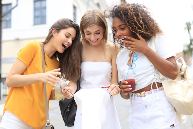 Mooie meisjes met boodschappentas die aankopen bespreken en glimlachen tijdens het wandelen in de stad.