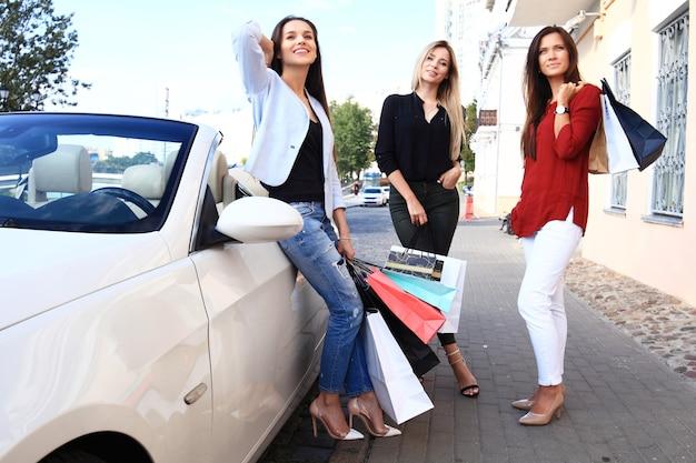 Mooie meisjes met boodschappentassen bespreken aankopen en glimlachen terwijl ze op hun auto leunen