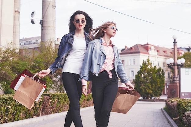 Mooie meisjes met boodschappentassen wandelen in het winkelcentrum.