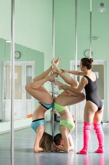 Mooie meisjes met een pyloon, vrouwelijke paaldanseressen die op een paal dansen.