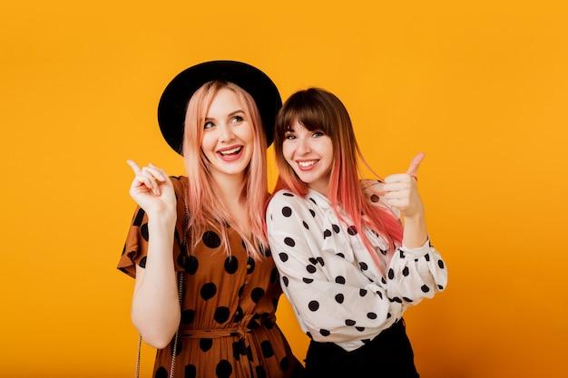 Mooie meisjes met emotionele gezicht poseren over gele muur