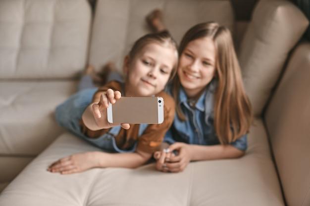 Mooie meisjes nemen selfies op hun telefoon terwijl ze op de bank liggen. zusters nemen een pauze van huiswerk en maken foto's tijdens quarantaine