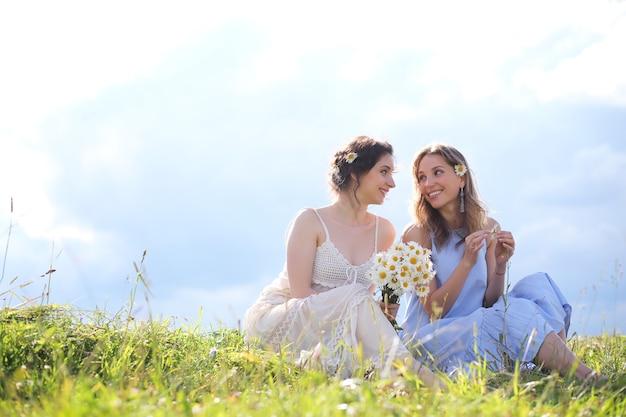 Mooie meisjes op een zomerse dag wandelen over het veld in sarafans