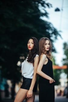 Mooie meisjes poseren in de stad op straat