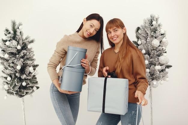 Mooie meisjes staan in een studio met cadeautjes