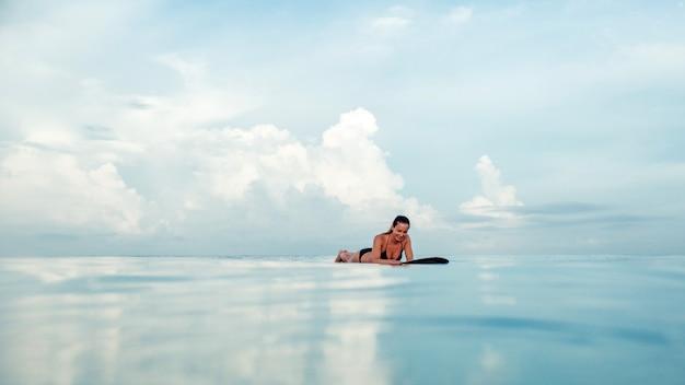 Mooie meisjes stellende zitting op een surfplank in de oceaan