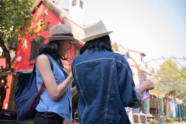 Mooie meisjes vinden een toeristische plek op de kaart.