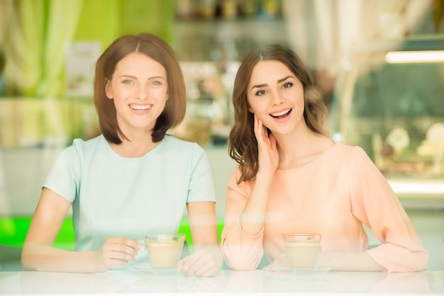 Mooie meisjes zitten in stedelijke café en koffie drinken.