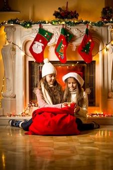 Mooie meisjes zitten naast de open haard en kijken naar de cadeaus van de kerstman