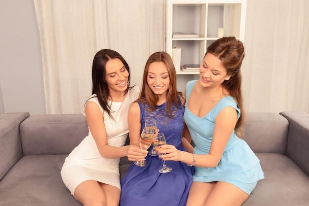 Mooie meisjes zittend op de bank en rammelende met glazen wijn