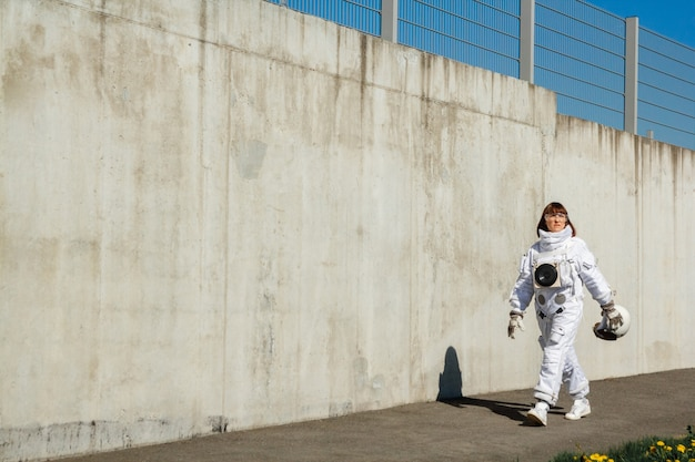 Mooie meisjesastronaut zonder helm op de achtergrond van een grijze muur. fantastisch ruimtepak.