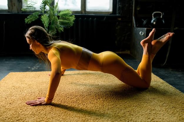 Mooie meisjesatleet die pushups doet in een moderne sportschool met grote ramen