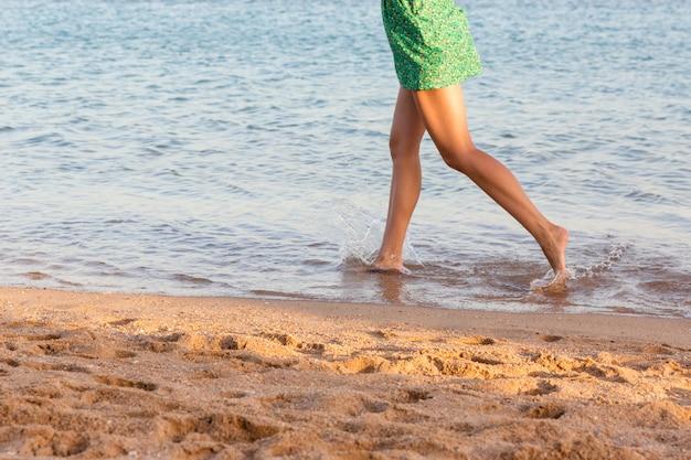 Mooie meisjesbenen die op het strand lopen. mooi meisje dat op water loopt