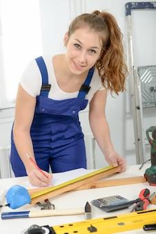Mooie meisjesbouwer die een plank van hout meten