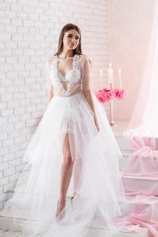 Mooie meisjesbruid in een wit de kledingslinnen van het kanten boudoir dat met een sluier wordt gesloten