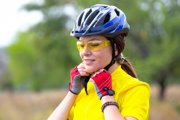 Mooie meisjesfietser in geel die een helm draagt. sport en recreatie.