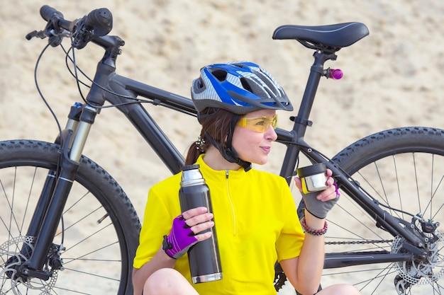 Mooie meisjesfietser in geel met thee en thermos in hand op de achtergrond van zand. sport en recreatie.