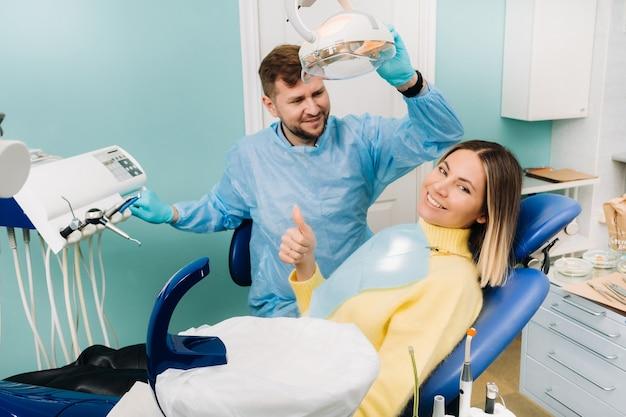 Mooie meisjespatiënt toont de klas met haar hand terwijl ze in de tandartsstoel zit.