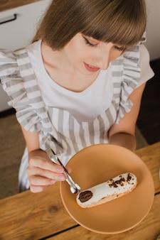 Mooie meisjespatissier of huisvrouw met een bord met eclairs kookcursus of banketbakkerij