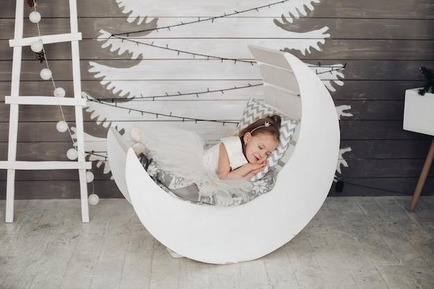 Mooie meisjesslaap in bed tegen geschilderde kerstboom.