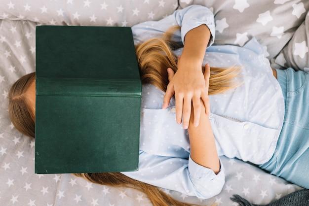Mooie meisjesslaap met een boek op haar gezicht