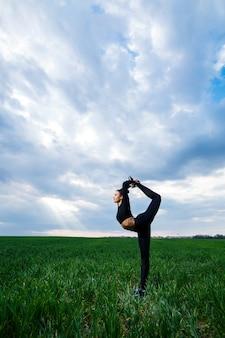 Mooie meisjesturner op het groene gras doet yoga. een mooie jonge vrouw op een groen gazon voert acrobatische elementen uit. flexibele turnster in het zwart doet een handstand in split