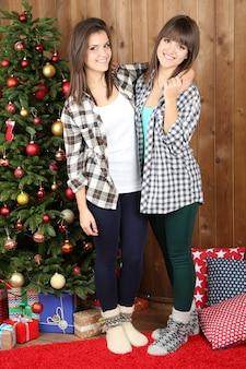 Mooie meisjestweeling in de buurt van de kerstboom thuis