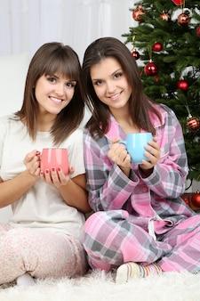 Mooie meisjestweeling in pyjama bij de kerstboom thuis