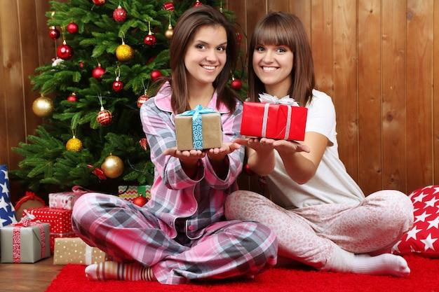 Mooie meisjestweeling in pyjama dichtbij kerstboom thuis