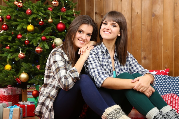 Mooie meisjestweelingen dichtbij kerstboom thuis