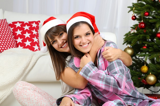 Mooie meisjestweelingen in pyjama dichtbij kerstboom thuis