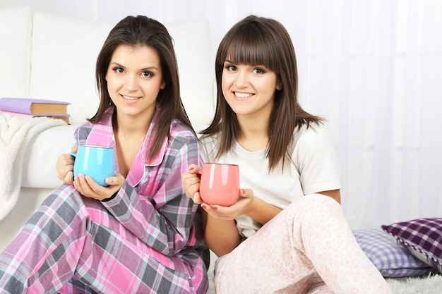 Mooie meisjestweelingen in pyjama's die thuis thee drinken