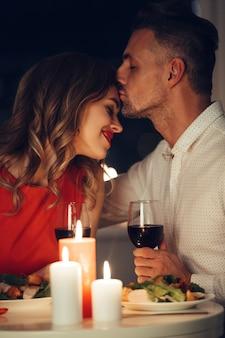 Mooie mens die zijn glimlachende gelukkige dame kust terwijl romantisch diner heeft