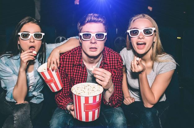 Mooie mensen met een bril kijken recht vooruit. ze hebben hun mond opengedaan. elk van hen heeft een stuk popcorn in de hand. ze zien er opgewonden uit