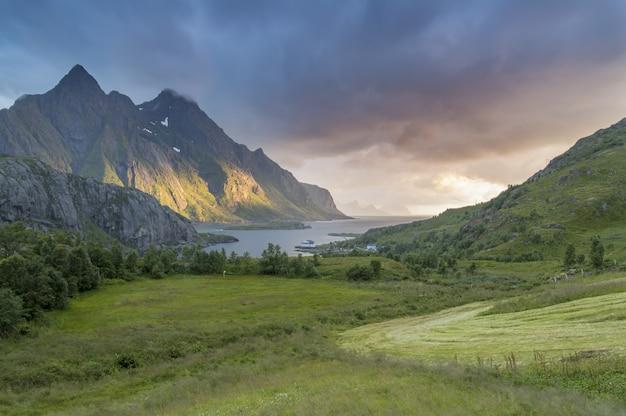 Mooie met gras bedekte vallei aan een meer met een prachtige berg