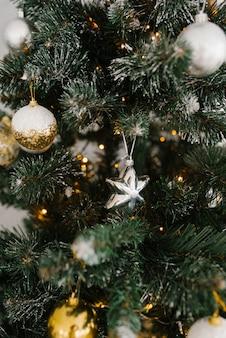 Mooie metalen en gouden kerstboomversieringen op een kerstboom.