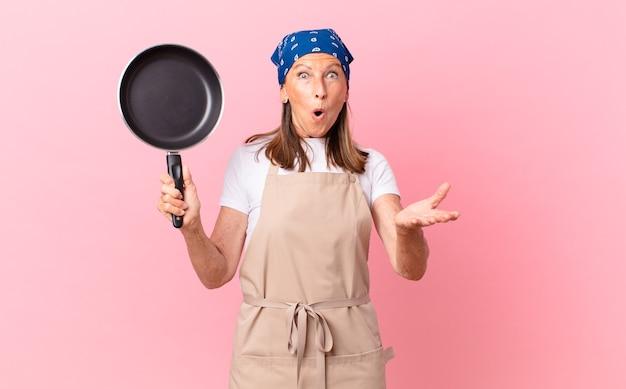 Mooie middelbare leeftijd vrouw verbaasd, geschokt en verbaasd met een ongelooflijke verrassing en met een pan. chef-kok concept