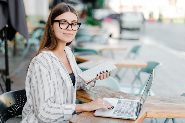 Mooie millenial bedrijfsvrouw die aan laptop in openlucht met notitieboekje werkt