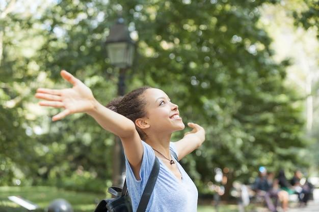 Mooie mixed-race jonge vrouw bij park, gevoel van vrijheid