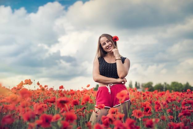 Mooie mode tiener meisje in warme zomerdag een papaverveld genieten van de natuur.