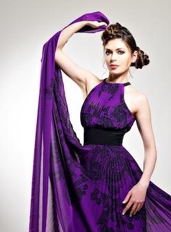 Mooie mode vrouw in paarse lange jurk kapsel met pigtails ontwerp, vormt in de studio